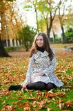 Girl sitting on the ground on a fall day. Girl sitting on the ground in park on a fall day royalty free stock image