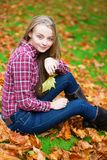 Girl sitting on the ground in fall park Stock Photos
