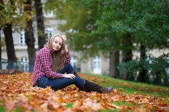 Girl sitting on the ground at fall royalty free stock image