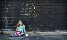 Girl sitting on ground next to brick wall Stock Photo