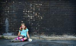 Girl sitting on ground next to brick wall Stock Photo