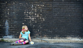 Girl sitting on ground next to brick wall Royalty Free Stock Photo