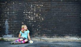 Girl sitting on ground next to brick wall Royalty Free Stock Photo