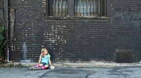 Girl sitting on ground next to brick wall Stock Images