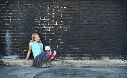 Girl sitting on ground next to brick wall Stock Photos