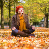Girl sitting on the ground in park on a sunny fall day Royalty Free Stock Images