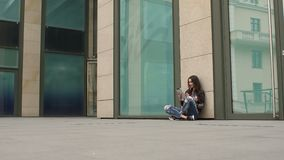 Girl sitting on ground with tablet leaning on wall stock video