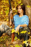 Girl sitting with a gun in his hand near a tree in the forest. Royalty Free Stock Photos