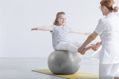 Girl sitting on gym ball. Smiling girl sitting on big gym ball working with physiotherapist Royalty Free Stock Photo