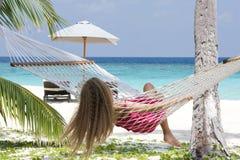 Girl sitting in hammock. Girl resting in hammock near blue ocean Stock Photo