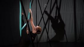 A girl is sitting in a hammock for yoga doing a cross-twine. An air yoga trainer sits in a hammock for yoga and shows a cross-twine stock footage