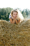 Girl sitting on hay Royalty Free Stock Photography