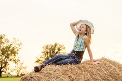 Girl sitting on a hay bale in the country Royalty Free Stock Images