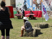 Girl sitting on hay. Watching performance during an American day,in France royalty free stock photos