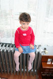 Girl sitting on heating system Royalty Free Stock Photos