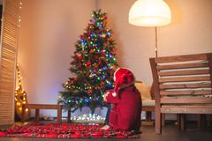 Girl is sitting with her back and looking at the Christmas tree Stock Images