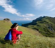 Girl sitting on a hill over sea Royalty Free Stock Photography