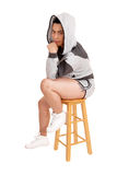 Girl sitting in hoodie on a chair. Stock Photography