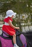 Girl is sitting in horse`s saddle. Little girl is sitting in horse`s saddle royalty free stock image