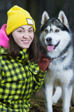 Girl sitting with husky dog. In forest Royalty Free Stock Photos