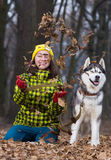 Girl sitting with husky dog. In forest Stock Image