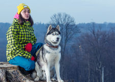 Girl sitting with husky dog. In mountains Stock Photos