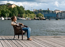 Girl Sitting In The Pier Stock Photo