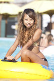 Girl sitting on inflatable ring on swimming pool Stock Photography