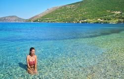 Girl sitting inside the sea at Ithaca Greece Royalty Free Stock Photo