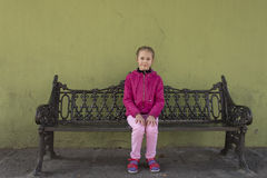 A girl is sitting on a iron bench Stock Image