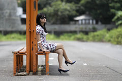 Girl sitting on an iron bench. A girl was sitting relaxed on a bench iron Stock Photo
