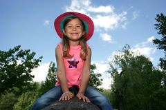 Girl sitting on an iron trunk Stock Photography
