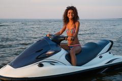 Girl sitting on a jet ski. African-american girl sitting on a jet ski Stock Photos