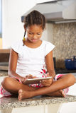 Girl Sitting On Kitchen Counter With Digital Tablet Stock Photography