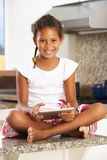 Girl Sitting On Kitchen Counter With Digital Tablet Stock Photos