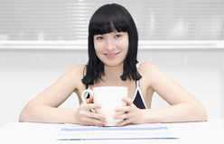 Girl sitting at the kitchen with a cup Stock Photography