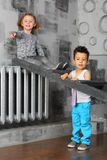 Girl sitting on a ladder and boy stands beside Royalty Free Stock Photos