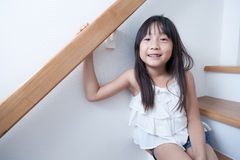 Girl sitting in on the ladder Stock Photo