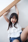 Girl sitting in on the ladder Royalty Free Stock Image