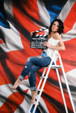 Girl sitting on the ladder and holding Movie Slate Royalty Free Stock Photography