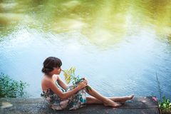 Girl sitting by a lake Royalty Free Stock Photo