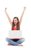 Girl sitting with laptop, arms raised. Young woman over white background Stock Image