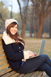 Girl sitting with laptop on bench in park Stock Photo