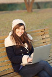 Girl sitting with laptop on bench in park Royalty Free Stock Image