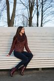 The girl is sitting on a large white bench. Dressed in jeans, a leather jacket and boots Stock Image
