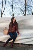 The girl is sitting on a large white bench. Dressed in jeans, a leather jacket and boots Stock Images