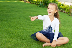 Girl sitting on the lawn. Сute little girl sitting on a green lawn shows a finger Stock Images