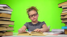 Girl sitting and leafing through the book. Green screen. Slow motion stock footage