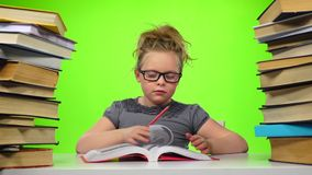 Girl sitting and leafing through the book. Green screen. Slow motion stock video footage