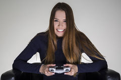 Girl sitting in a leather armchair and holding a video game controller. Royalty Free Stock Photography